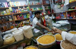 "The owner of a ""Kirana"" or mom-and-pop grocery store accepts money from a customer in his shop in Mumbai December 7, 2012. The Indian government won a second parliament vote on Friday on allowing foreign supermarkets into the country, paving the way for Prime Minister Manmohan Singh to press ahead with more reforms, including freeing up a cash-strapped insurance sector. REUTERS/Vivek Prakash (INDIA - Tags: BUSINESS FOOD) - RTR3BBCP"